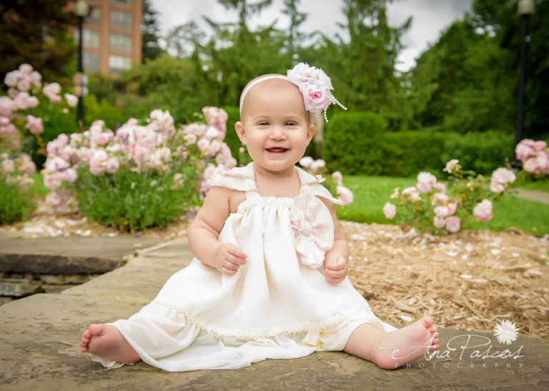 baby-girl-sitting-in-front-of-roses-for-outdoor-family-portraits-in-toronto